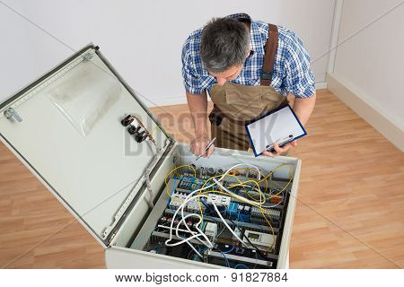 Electrician Looking At Fuse Box