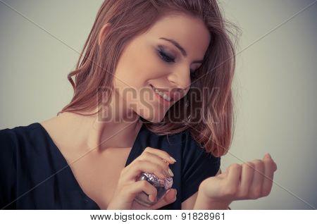 Beautiful teenage girl applying perfume on her hand