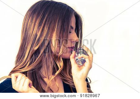 Beautiful teenage girl smelling perfume
