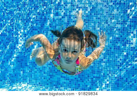 Happy active underwater child swims in pool, beautiful healthy girl swimming and having fun