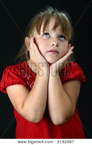 Small girl holding her cheeks with her hands on black