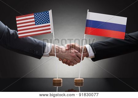 Businesspeople Shaking Hands With Us And Russia Flags
