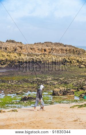 OUALIDIA, MOROCCO, APRIL 6, 2015: Fishermen with rod and caught octopus walks along beach