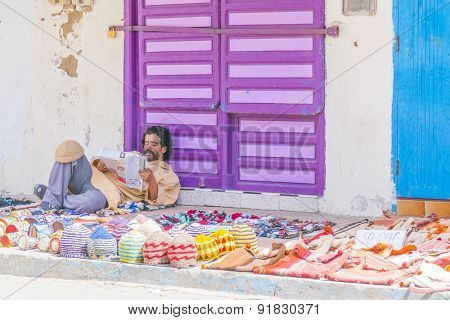AS-SAWIRA, MOROCCO, APRIL 7, 2015: Street seller of handmade woolen caps waits for customers reading a newspaper