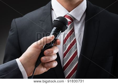 Person Holding Microphone In Front Of Businessman