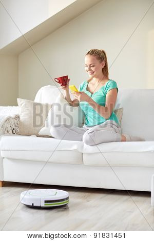 people, housework and technology concept - happy woman with smartphone and robot vacuum cleaner drinking tea at home