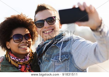 friendship, relations, tourism, travel and people concept - happy teenage friends or couple in sunglasses with smartphone taking selfie outdoors