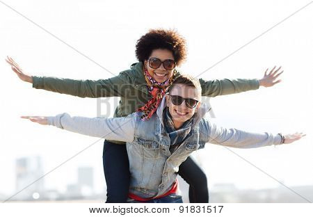 friendship, leisure, international, freedom and people concept - happy teenage couple in shades having fun outdoors
