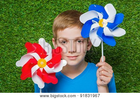 Smiling boy holding pinwheels over grass close up