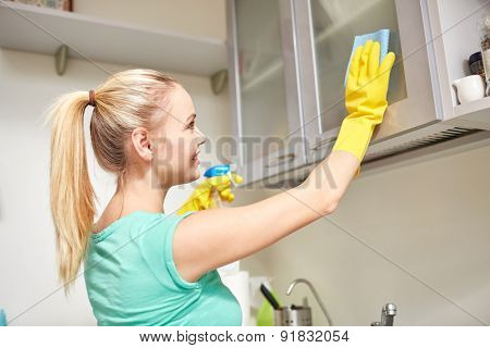 people, housework and housekeeping concept - happy woman cleaning cabinet with rag and cleanser at home kitchen