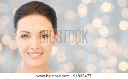 beauty, people, holidays, luxury and health concept - beautiful young woman face over lights background