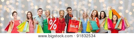 consumerism, people and discount concept - group of happy people with percentage and sale sign on shopping bags over holidays lights background