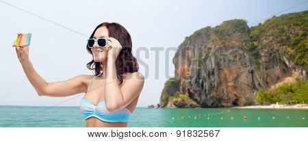people, technology, summer and beach concept - happy young woman in bikini swimsuit and sunglasses taking selfie with smatphone over sea and rock background