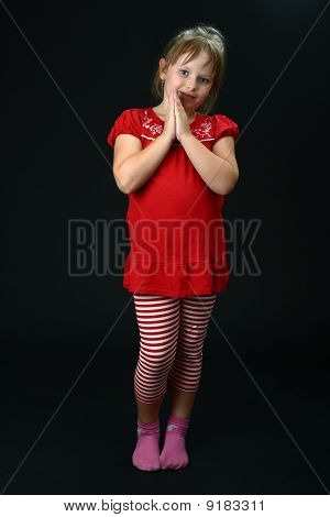 Curious small girl with clasped hands smiling on black