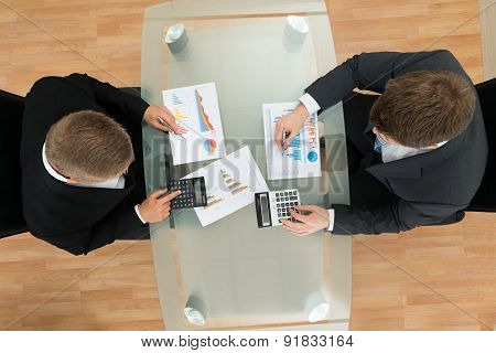 Businessmen With Pen And Calculator Analyzing Graph