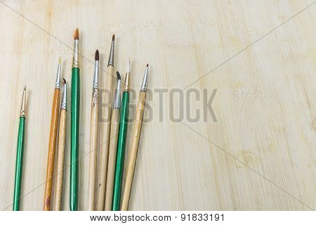 Used Artist Paint brushes On Wood Background