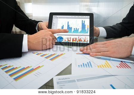 Two Businessman Discussing Graph On Digital Tablet