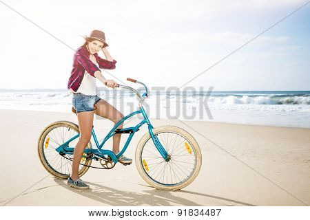 Beautiful young woman riding her bicycle at the beach