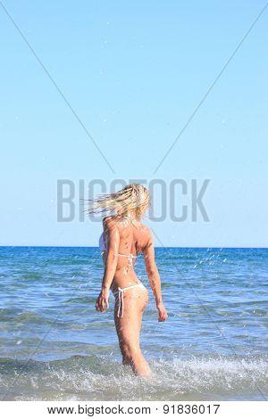Young blonde woman having fun in the sea