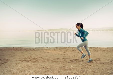 Young Woman Running On Coastline