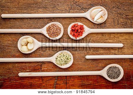 superfood abstract (garlic cloves, goji berry, chia, hemp, flax seeds, macadamia,nuts) - top view of wooden spoons against rustic grunge wood