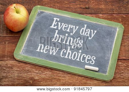 Every day brings new choices - motivational positive words on a slate blackboard against red barn wood