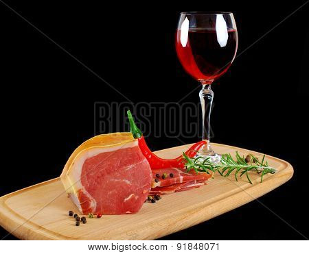 Meat and glass of wine on black background