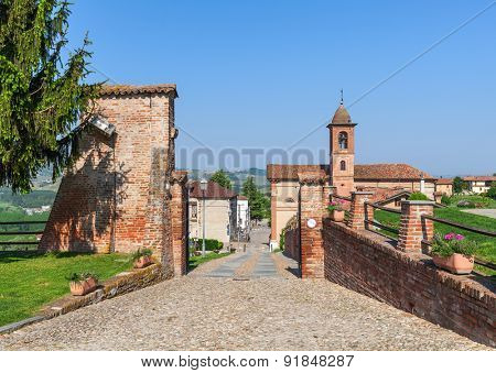 Narrow cobblestone walkway among brick walls as small church on background under blue sky in Piedmont, Northern Italy.