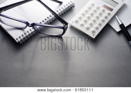 Office Supplies And Eyeglasses On Grey Desk