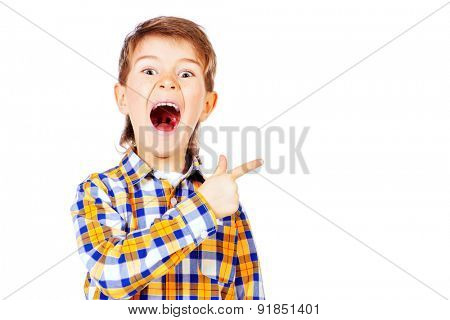 Portrait of a cute boy pointing the finger in the direction and screaming. Healthcare. Education. Isolated over white.