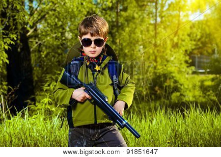 A boy playing with a toy rifle outdoor. Military concept. Childhood.