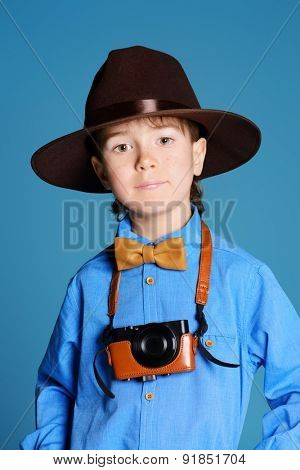 Portrait of a cute 7 year old boy in elegant hat and bow-tie making photographs by his camera. Occupations.