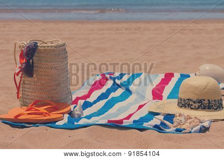 sunbathing accessories on sandy beach in straw bag