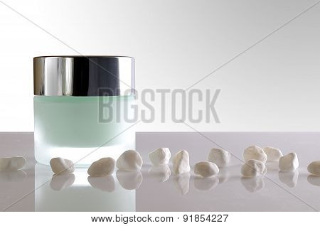 Cream Jar Closed And Small White Stones Isolated