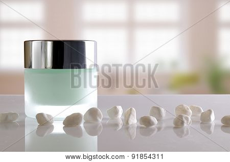 Cream Jar Closed And Small White Stones Windows Background