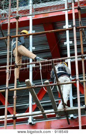 Dos constructores en un andamio de acero