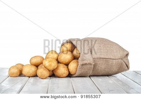 New Potatoes In A Bag On A White Wooden Table On Isolated On A White Background