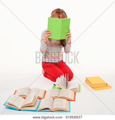 Little girl sitting on floor with books