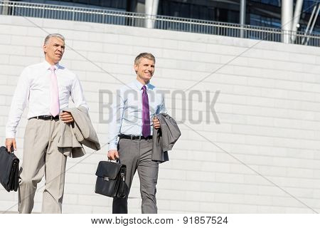 Middle-aged businessmen with briefcases against wall