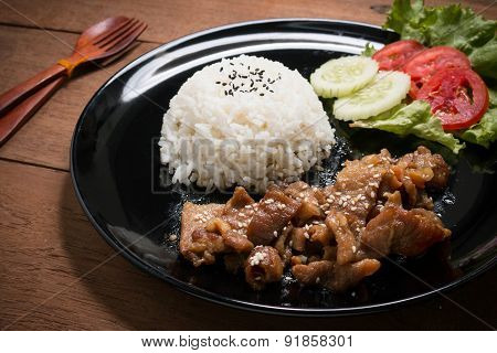 Sweet Pork with Steam Rice, On Black Dish And Wooden Table.