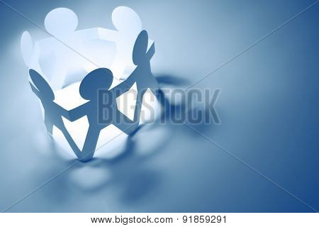 Team of paper doll people holding hands. Blue tone