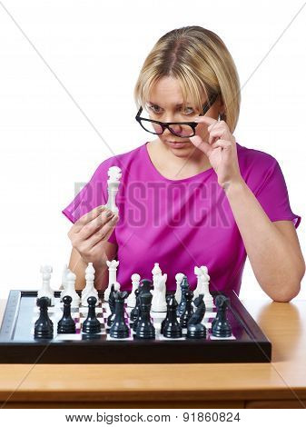 Woman In Glasses Examines Chess King Isolated