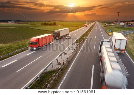 Driving Trucks In Motion Blur On The Highway At Sunset