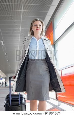 Young businesswoman with luggage walking in railroad station