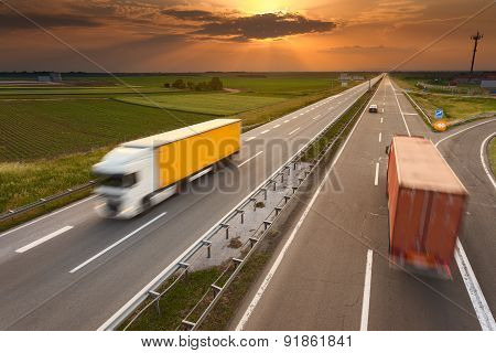 Two Trucks In Motion Blur On The Highway At Sunset