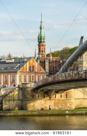 KRAKOW, POLAND - CIRCA APR, 2015: Vistula river, footbridge and Church St.Joseph in background. Krakow is visited by over 8 million tourists a year, number of foreign tourists up to 2 million people.