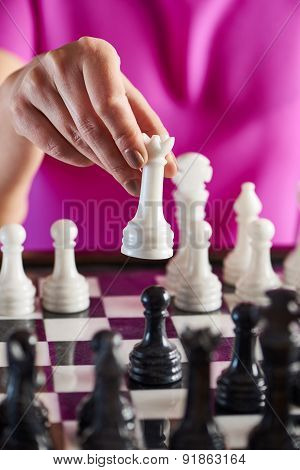 Hand With White Queen Over Chessboard