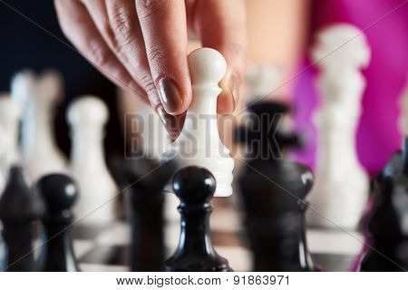 Hand With White Pawn Over Chessboard