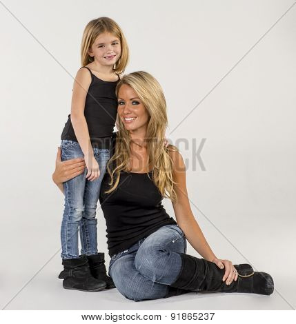 A mother and daughter pose in a studio environment