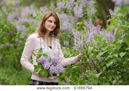 Young Girl Breaks Lilac Flowers